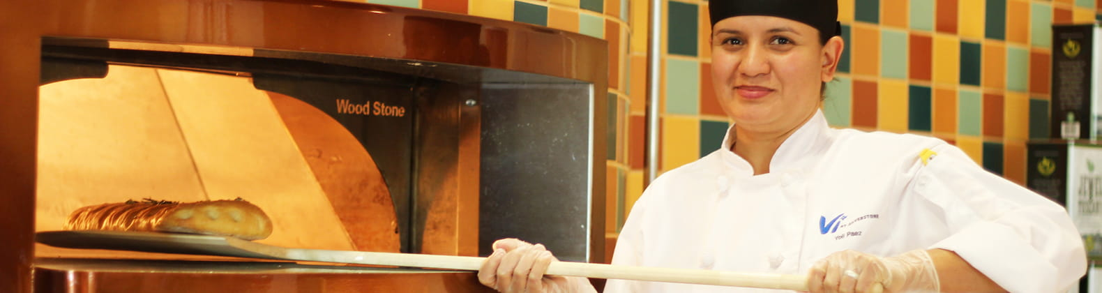 chef takes bread out of wood stone oven at retirement community