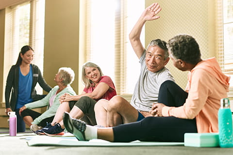 People talking and stretching in a group exercise class