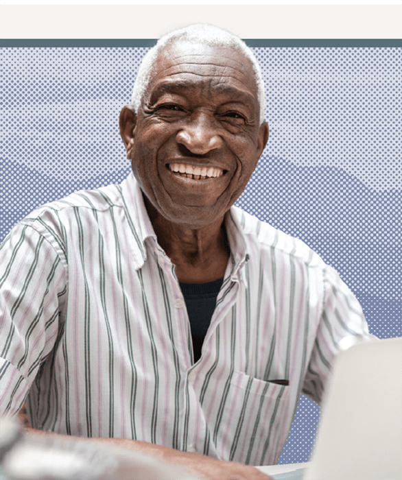 A smiling man sitting with his laptop
