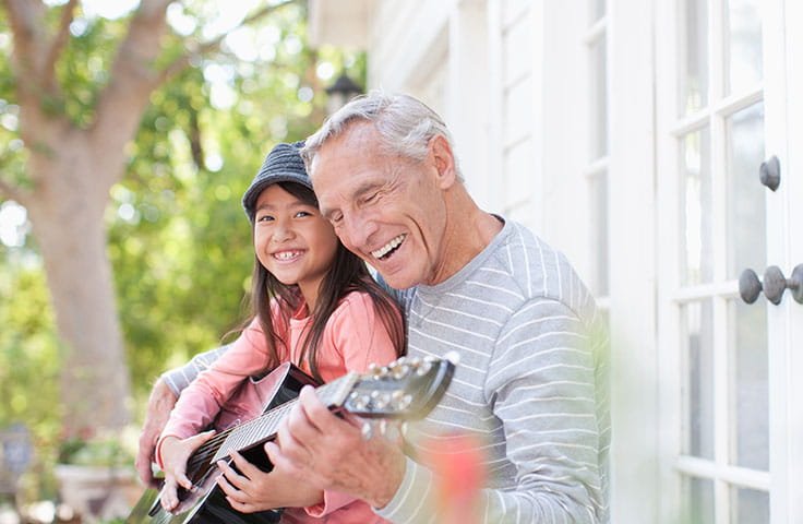 An older gray-haired man plays guitar with a young girl
