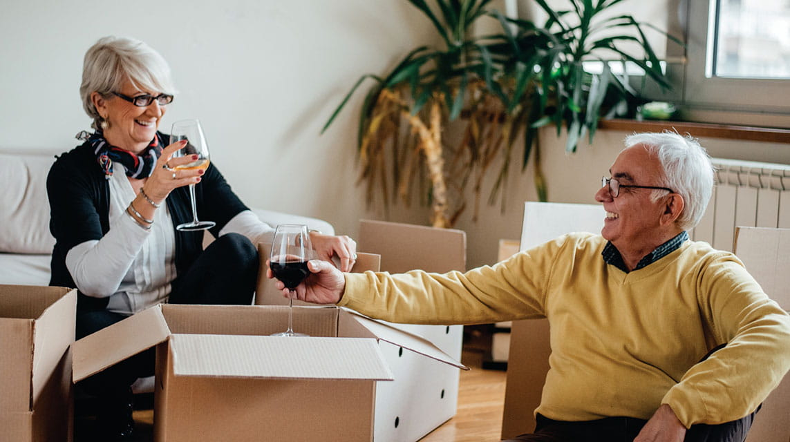 Man and woman drinking wine while packing